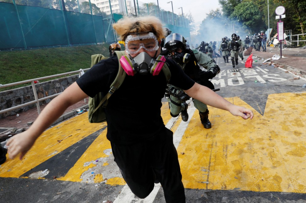 A university student runs from riot police at the Chinese University of Hong Kong