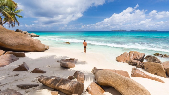 Man enjoying Anse Patates picture perfect beach on La Digue Island Seychelles model released Symbo