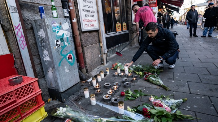 A man lays down flowers as a restaurant employee sweeps broken glass at the site where a 15-year-old was fatally hit and another severely wounded when attackers opened fire on a pizzeria before fleeing the scene on bicycles in Malmo
