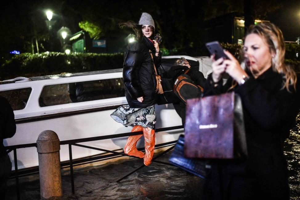 Balanceakt: Eine junge Frau hat sich in Venedig auf ein Geländer gerettet, während die italienische Touristenmetropole mit dem schlimmsten Hochwasser seit über 50 Jahren zu kämpfen hat.
