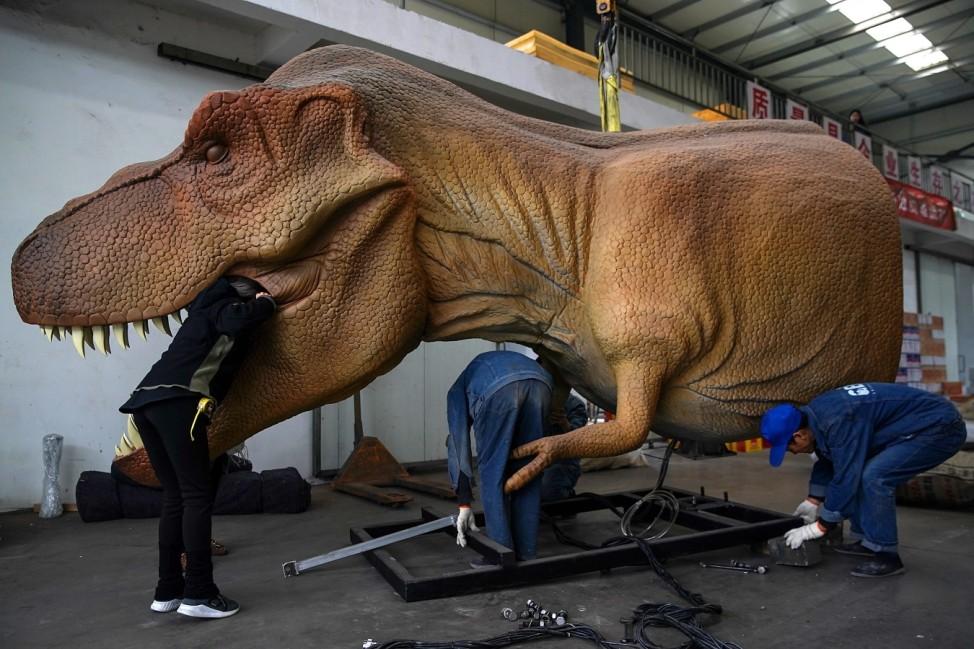 Gezähmtes Monster: Mitarbeiter einer Dinosaurier-Fabrik im chinesischen Zigong machen eine elektronische Riesenechse fit für ihren Einsatz.