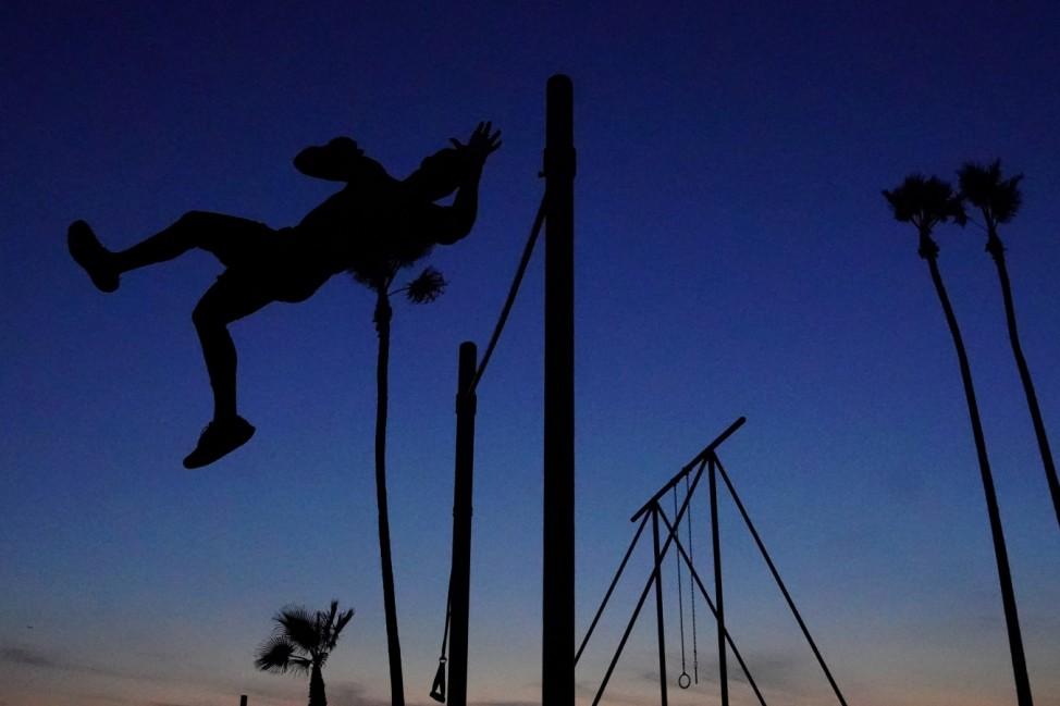 """Flugschau: Ein Mann zeigt sein Können an einem Reck am """"Venice Beach"""" von Los Angeles."""