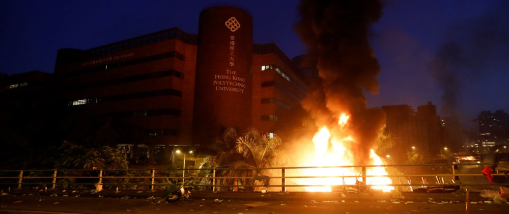 Protesters are seen next to a fire at Hong Kong Polytechnic University (PolyU) in Hong Kong