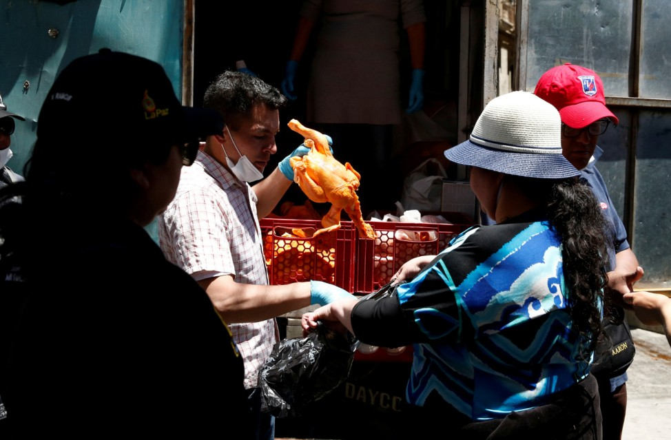 A woman receives a chicken due to food shortage caused by blockades in recent days in La Paz