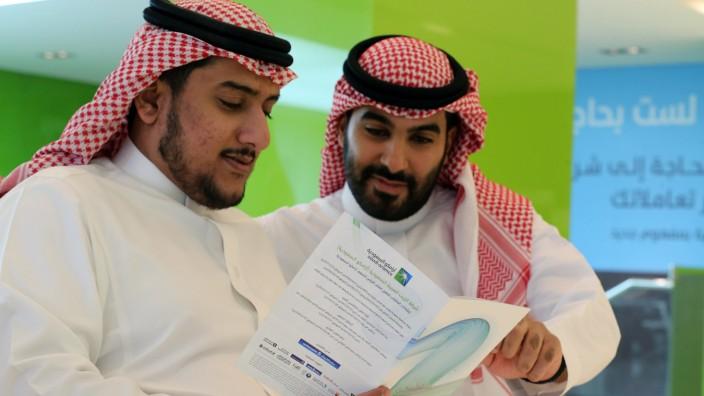 Saudi men check the prospectus of Aramco IPO, in Riyadh