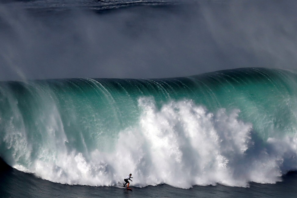 A surfer drops in on a large wave at Praia do Norte in Nazare