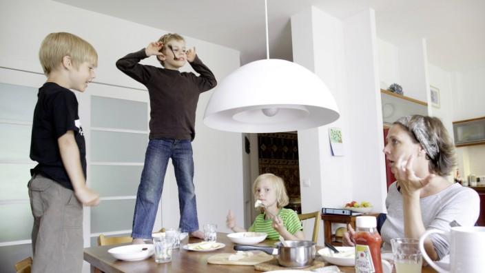 Ueberforderte Mutter mit ihren Kindern beim Essen Berlin Deutschland Overstrained Mother with he