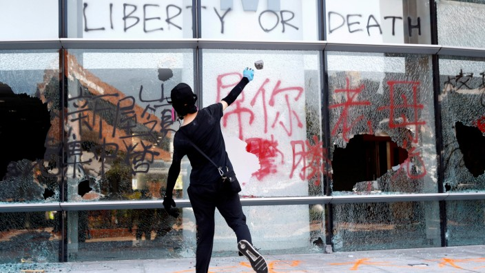 FILE PHOTO: A protester throws a stone into a building at Hong Kong Polytechnic University in Hong Kong,