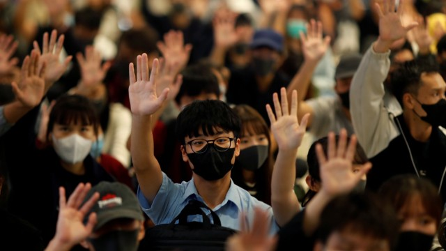 Protesters hold up their hands during an anti-government protest at Yoho Mall in Yuen Long, Hong Kong