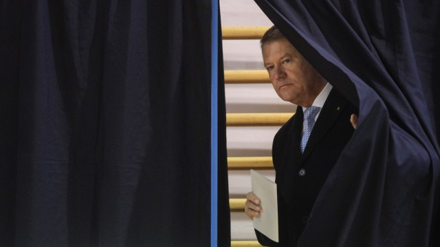 Incumbent candidate Klaus Iohannis leaves the polling booth in the second round of a presidential election