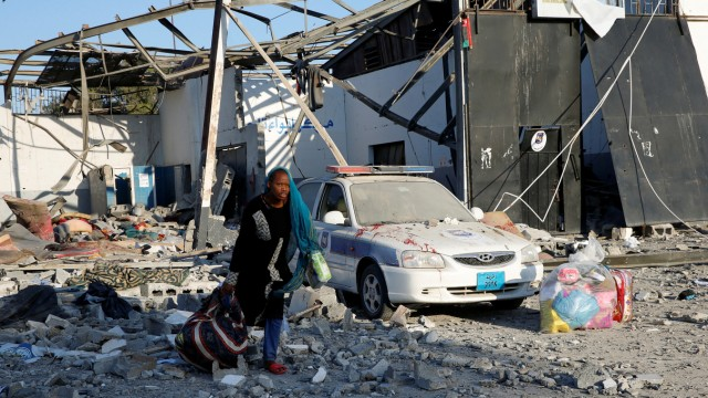 A migrant picks up her belongings from among rubble at a detention centre for mainly African migrants that was hit by an airstrike in the Tajoura suburb of the Libyan capital of Tripoli