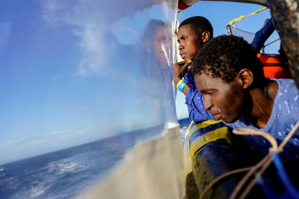 Migrants stand on board a NGO Proactiva Open Arms rescue boat in central Mediterranean Sea sailing to the Italian port of Taranto