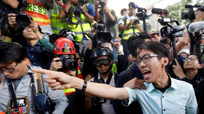 A pro-democratic winning candidate at district council local elections argues with police officers as they walk towards the campus of the Polytechnic University (PolyU) in Hong Kong