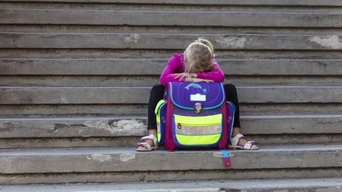 Sad little girl sitting on stairs with school bag model released Symbolfoto PUBLICATIONxINxGERxSUIx