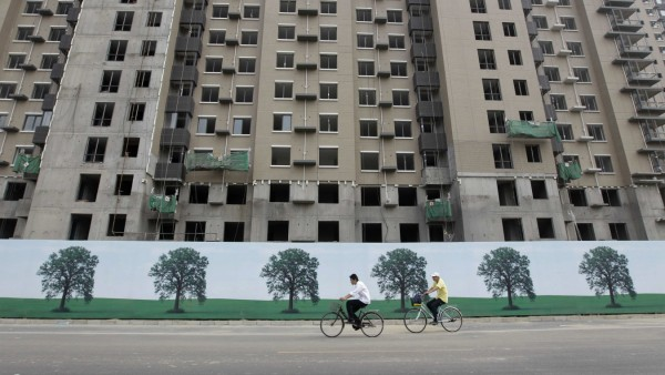 People cycle past apartment blocks under construction in Beijing