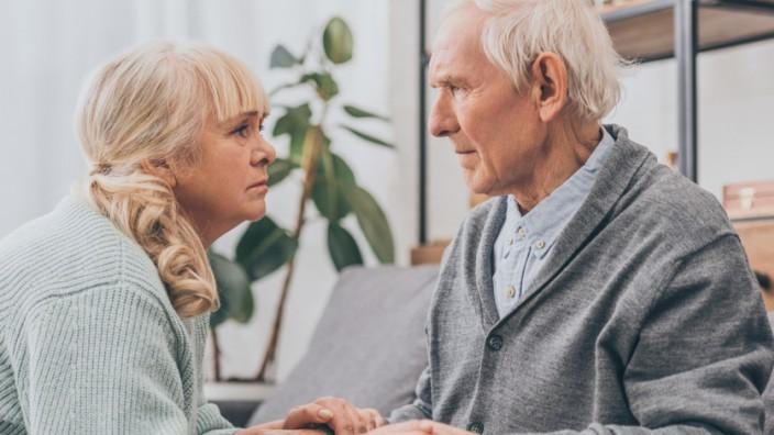 Eine Frau und ein Rentner sitzen im Wohnzimmer, sie hält seine Hände. Die Pflege von Angehörigen ist ein Kraftakt.