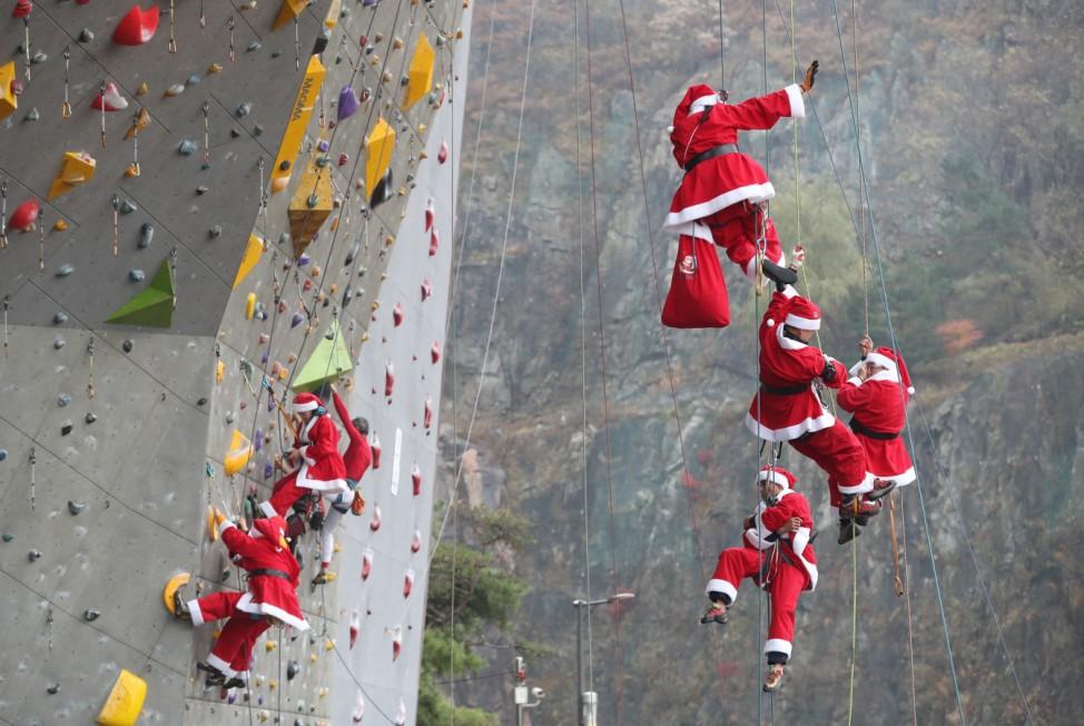 Weihnachtsmänner an einer Kletterwand