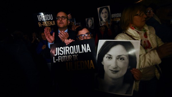 People gather outside the Maltese Prime Minister's office calling for the resignation of Joseph Muscat, in Valletta