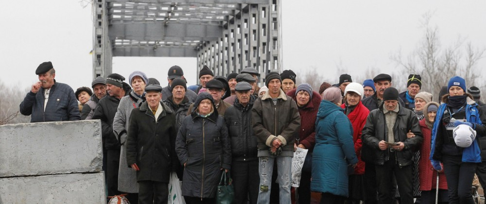 People cross a bridge under restoration in Stanytsia Luhanska