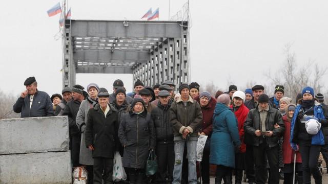 People cross a bridge under restoration in Stanytsia Luhanska
