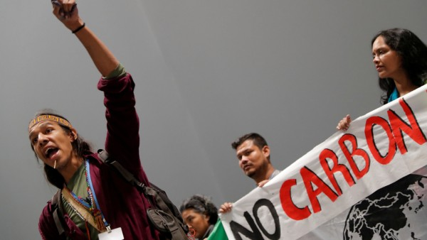 An activist speaks during a protest about the destruction brought by carbon markets and carbon offsets inside the venue of the U.N. climate change conference (COP25) in Madrid