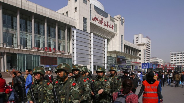 Armed police patrol near the exit of the South Railway Station, following Wednesday's bomb and knife attack, in Urumqi