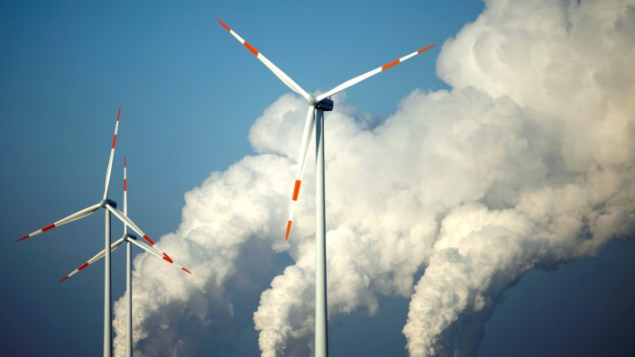 FILE PHOTO: Steam billows from the cooling towers of Vattenfall's Jaenschwalde brown coal power station behind wind turbines near Cottbus