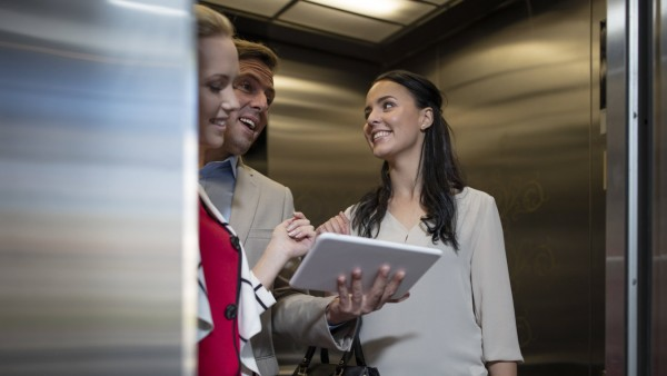 Business people in elevator with tablet talking model released Symbolfoto property released PUBLICAT