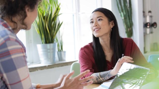 Two women talking at table in office model released Symbolfoto property released PUBLICATIONxINxGERx