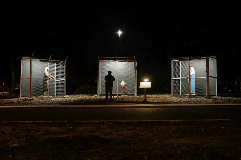 A man view sculptures of Jesus, Mary and Joseph depicted as refugees in cages at a Nativity scene  in Claremont