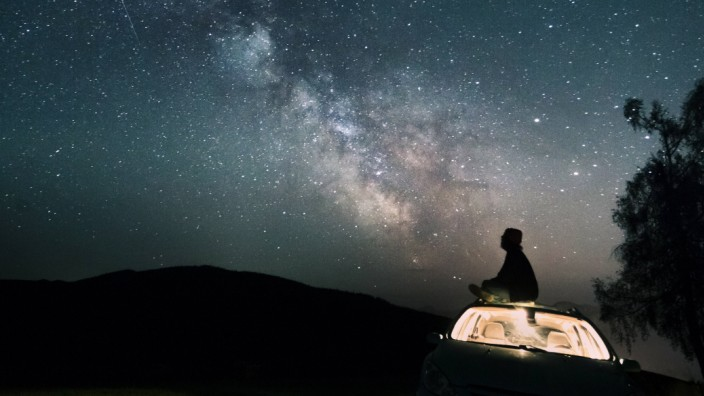 Austria Mondsee silhouette of man sitting on car roof under starry sky model released Symbolfoto P