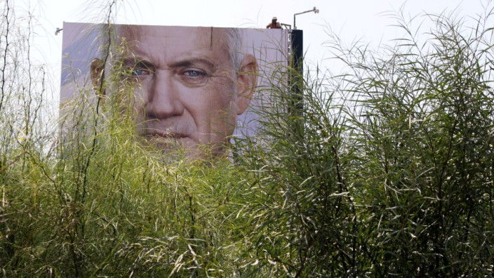 FILE PHOTO: Labourers hang an election campaign banner depicting Benny Gantz, the leader of Blue and White party, in Tel Aviv, Israel