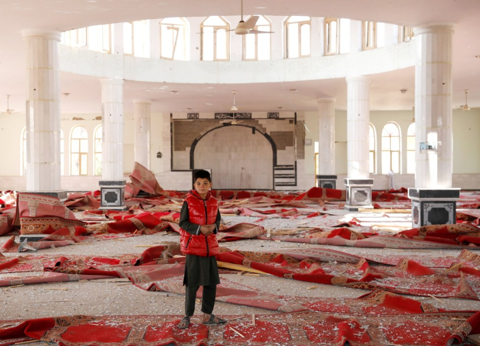 An Afghan boy stands inside a damaged mosque at the site of an attack in a U.S. military air base in Bagram