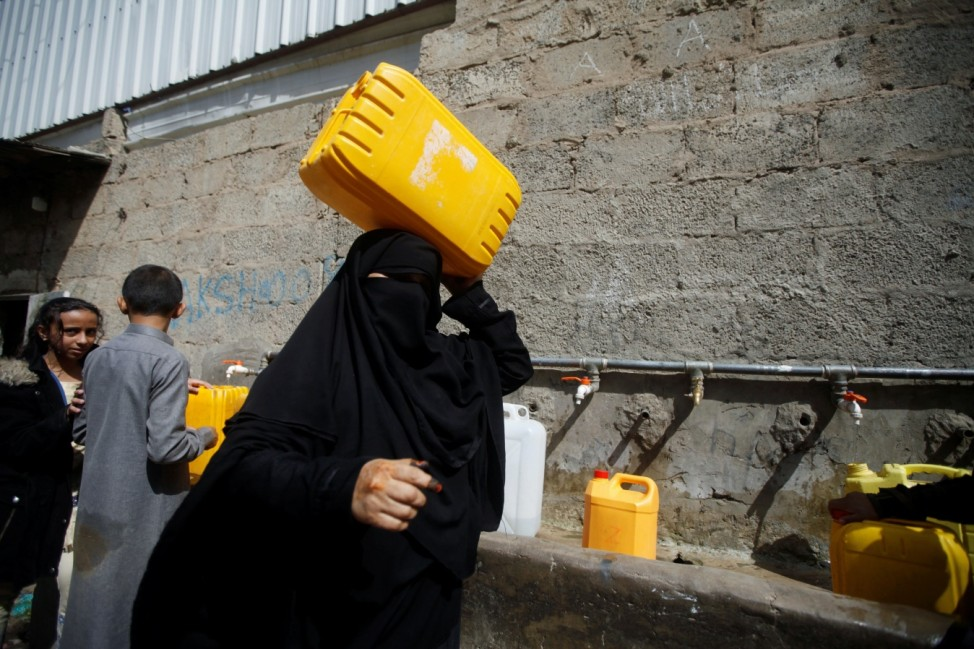 People collect water from a charity tap amid a shortage of drinking water supplies in Sanaa
