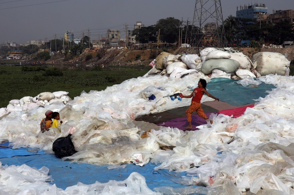 Girl plays with a toy gun at a plastics recycling yard in Dhaka