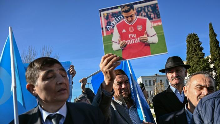 Uiguren halten ein Foto von Mesut Özil bei einer Demonstration in die Höhe
