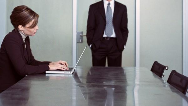 Woman sitting at table using laptop man standing in front of door PUBLICATIONxINxGERxSUIxAUTxONLY C