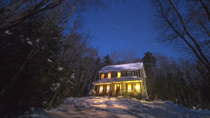 A warm house in the woods glows under a starlit sky PUBLICATIONxINxGERxSUIxAUTxONLY Copyright xTys