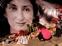 FILE PHOTO: People lay flowers and candles at a makeshift memorial during a vigil and protest on the first anniversary of the assassination of anti-corruption journalist Daphne Caruana Galizia in a car bomb, outside the Courts of Justice in Valletta