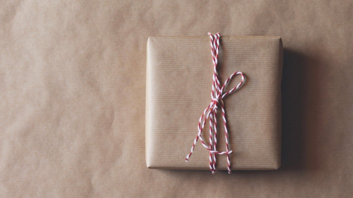 Wrapped Christmas present on a matching brown paper background PUBLICATIONxINxGERxSUIxAUTxONLY Copyr