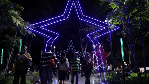 People gather in a square decorated with Christmas lights in Caracas