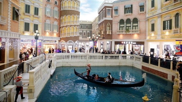 People take a gondola ride inside the shopping mall of the Venetian Macao hotel and casino in Macau