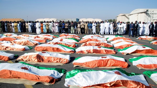 Families and officials pray in front of the flag-draped soldiers, killed during an attack on the army camp on the Niger- Mali border, during their burial ceremony at military airport in Niamey