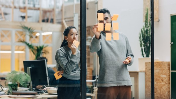 Colleagues discussing while sticking adhesive notes on glass wall in office