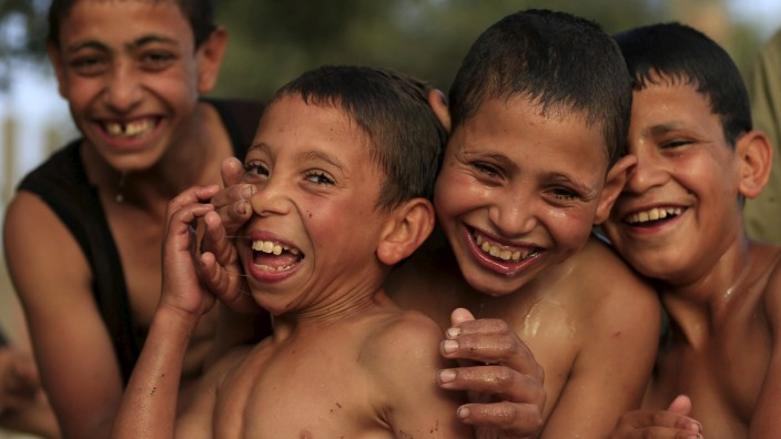 Egyptian boys laugh and smile after jump into the River Nile to cool off in Minya south of Cairo