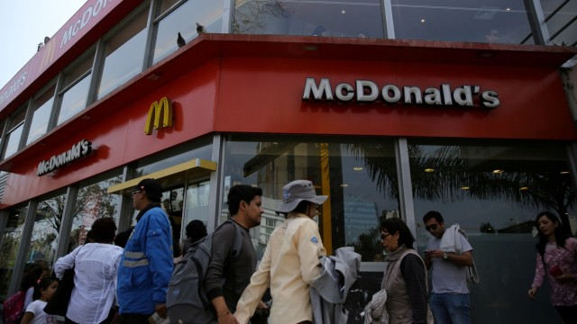 FILE PHOTO: People walk past McDonald's fast-food restaurant in Lima