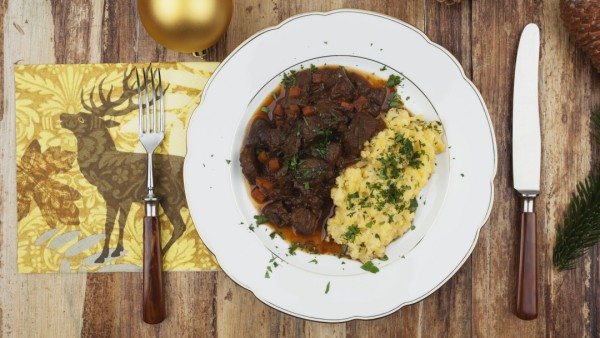 Plate of cooked venison goulash with mashed potatoes and Christmas decoration on wooden background P