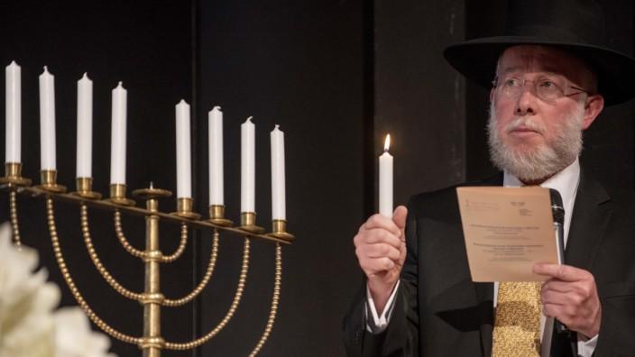 Rabbiner Shmuel Aharon Brodman entzündet nach den Reden die Chanukka-Kerze.