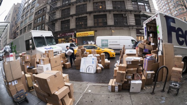 Delivery services expect record volume of deliveries for the holidays A FedEx worker sorts deliverie