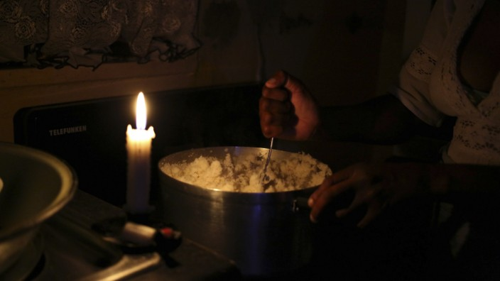 A woman stirs Uphutu, a local staple food made from mielie-meal (ground maize), during a blackout in Soweto